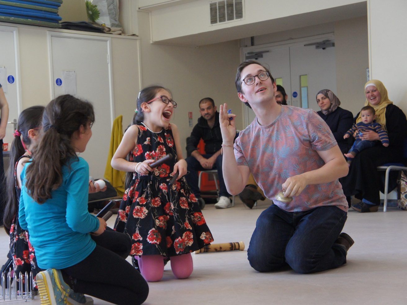 An excited young girl playing a percussion instrument with a workshop leader.