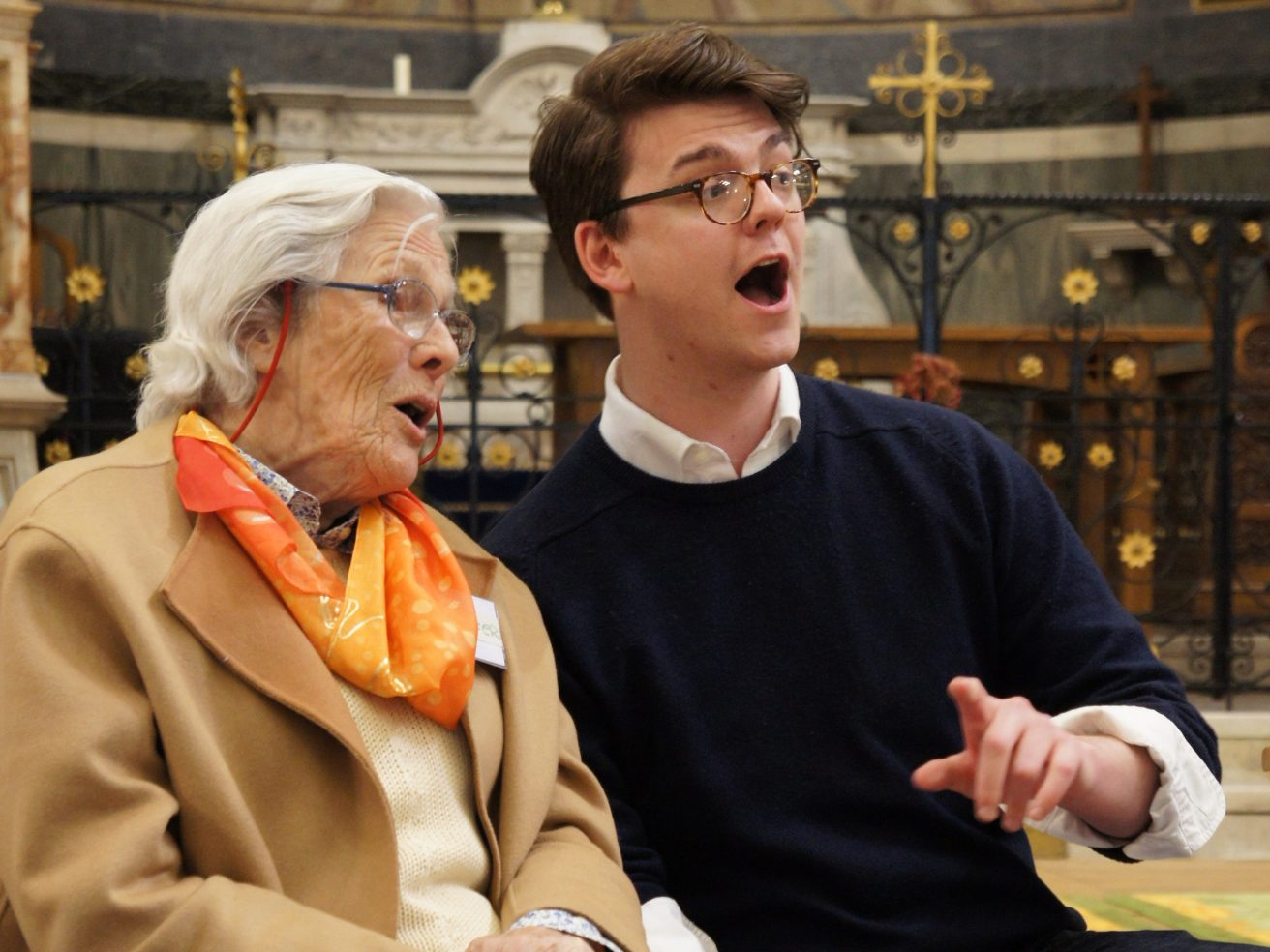 Two people singing together in a church