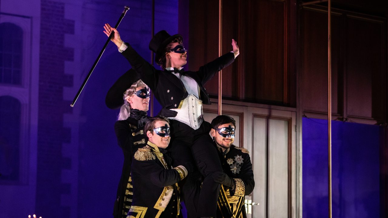 Alison Langer as Oscar with members of the Opera Holland Park Chorus in Un ballo in maschera at Opera Holland Park © Ali Wright